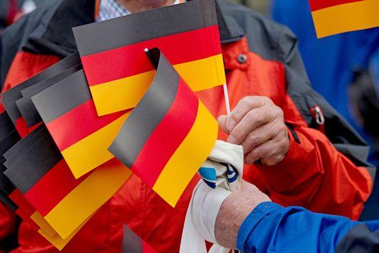 Deutschland-Flaggen werden am Sonntag (03.10.2010) vor dem Rathaus in Bremen bei den zentralen Feierlichkeiten zum Tag der deutschen Einheit verteilt. Bremen ist Gastgeber der Jubiläumsfeiern, weil es zurzeit den Vorsitz im Bundesrat hat. Foto: Friso Gentsch dpa/lni